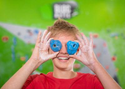 Junger Mann hält sich blaue Bouldergriffe vor die Augen